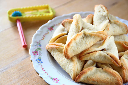 Hamantaschen cookies or hamans ears and noisemaker for Purim celebration (jewish holiday)