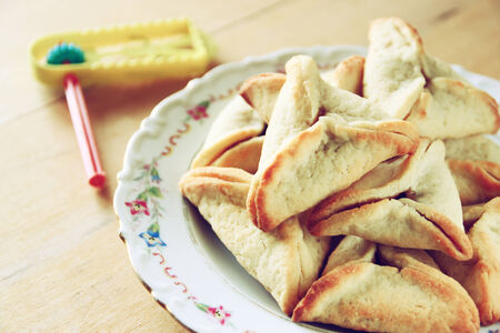 megillah: Hamantaschen cookies or hamans ears and gragger for Purim celebration (jewish holiday)