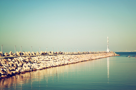 marina water: marina with the lighthouse and the sea. vintage filtered image