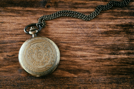 macro image of old vintage pocket watch on wooden table. top view. retro filtered image photo