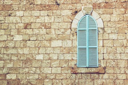 old house wall from jerusalem stone and old blue iron shutters. retro filtered image