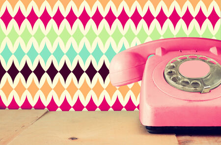 retro phone: Retro pastel pink telephone on wooden table and abstract retro geometric pastel pattern Background. retro filtered image