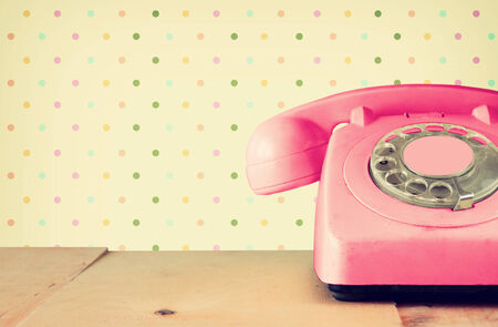 telephone: Retro pastel pink telephone on wooden table and abstract retro geometric pastel pattern Background. retro filtered image