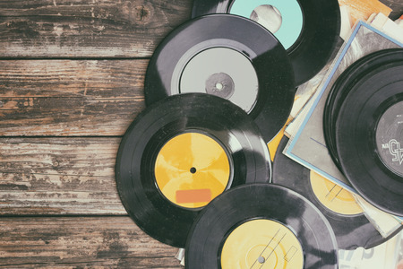 eighties: close up image of old records over wooden table , image is retro filtered .