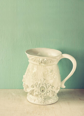 antique vase: white classic and antique vase on wooden table. filtered image