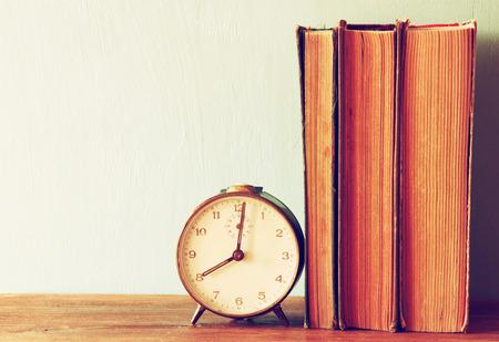 filtered: pila de libros antiguos y viejo reloj sobre la mesa de madera. imagen filtrada