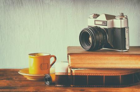 old camera over stack of books. vintage filter. photo