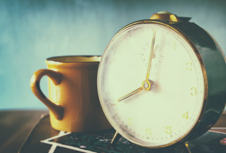 close up image of old clock and cofee cup over wooden table. image is filtered with retro faded style photo