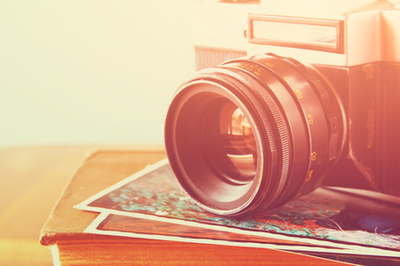close up image: close up photo of old camera lens over wooden table. image is retro filtered. selective focus Stock Photo