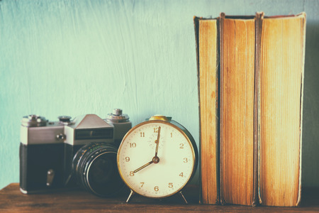stack of books, old clock and vintage camera over wooden table. image is processed with retro faded style Imagens