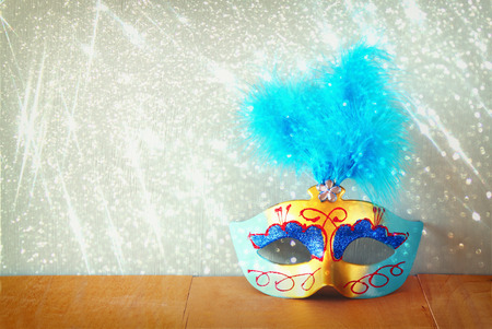 vintage Venetian masquerade mask on wooden table with glitter overlay photo