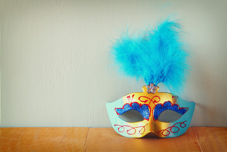 night table: Venetian masquerade mask on wooden table. retro filtered image