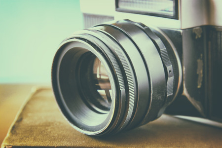 instagram: close up photo of old camera lens over wooden table. image is retro filtered. selective focus Stock Photo
