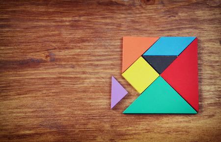 felülnézetben egy hiányzó darabja egy négyzet tangram puzzle, több fából készült asztal.
