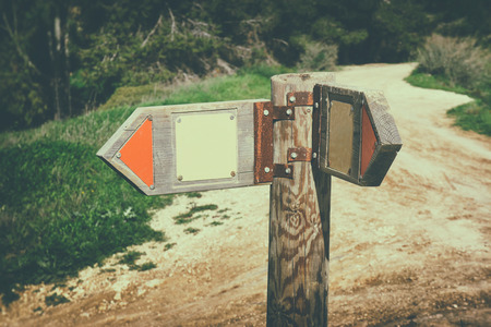 posts: signpost in countryside landscape. image is retro filtered with faded style .