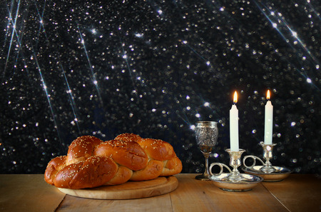 kiddush: Sabbath image. challah bread and candelas on wooden table. glitter overlay
