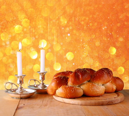 Sabbath image. challah bread and candelas on wooden table. glitter overlay photo