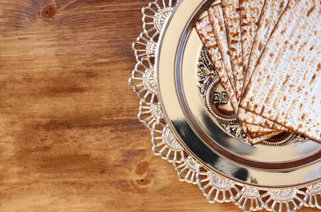 pesah: top view of passover background. egg and matzoh (jewish passover bread) over wooden background.