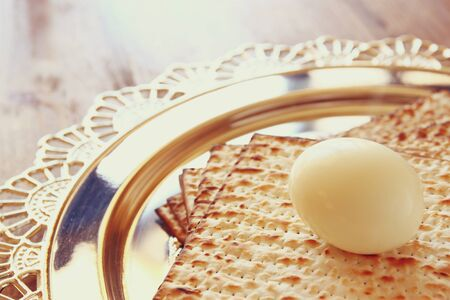 matzoth: top view of passover background. egg and matzoh (jewish passover bread) over wooden background.