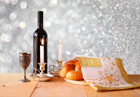 image: Sabbath image. challah bread and candelas on wooden table. glitter overlay
