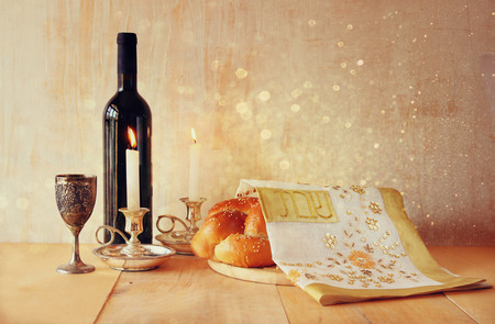 Sabbath image. challah bread and candelas on wooden table. glitter overlay