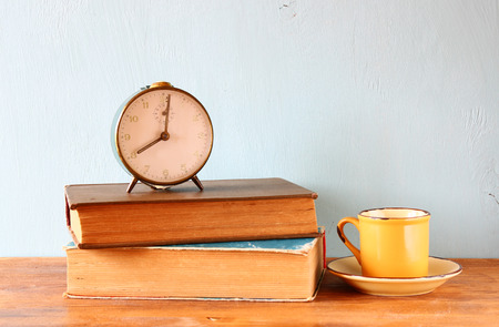 Image of old clock and coffee cup over wooden table photo