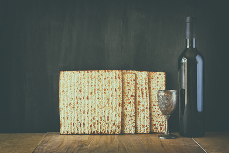 matzos: Passover background. wine and matzoh (jewish passover bread) over wooden background. image is filtered with retro faded style