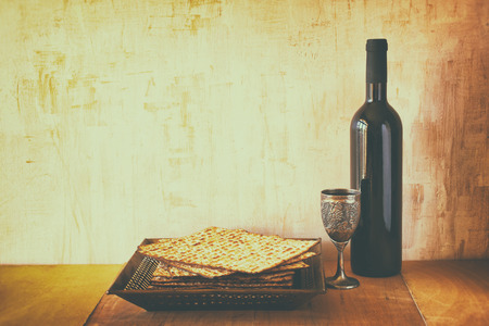 Passover background. wine and matzoh (jewish passover bread) over wooden background. image is filtered with retro faded style