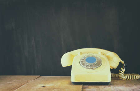 retro telephone: Retro telephone on wooden table. filtered image with faded retro style