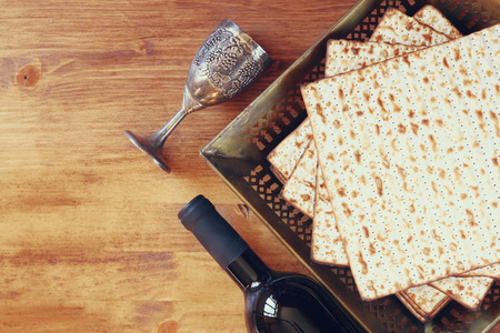 Top view of passover background. wine and matzoh (jewish passover bread) over wooden background.
