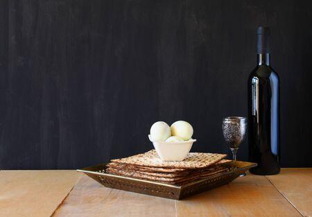 pesakh: passover background. wine and matzoh (jewish passover bread) over wooden background.