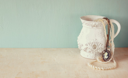 perlas: blanco cl�sico florero victoriana en mesa de madera con una colecci�n de joyas de �poca rom�ntica y perlas. filtrada retro imagen. espacio para texto Foto de archivo
