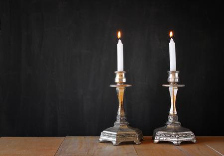 shabat: dos candelabros con velas encendidas sobre la mesa de madera y fondo de la pizarra