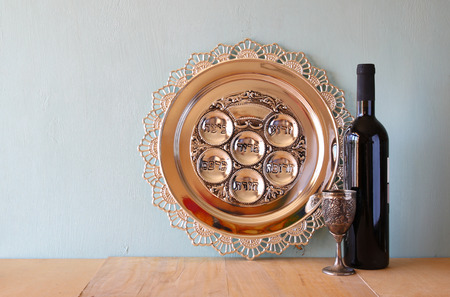 Passover background. wine and matzoh (jewish passover bread) over wooden background. photo