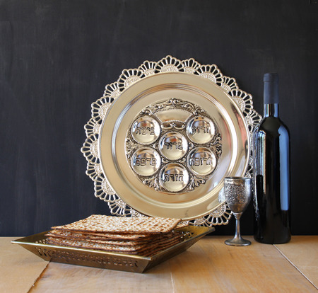 Passover background. wine and matzoh (jewish passover bread) over wooden background.