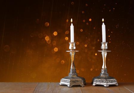 kerze: zwei Leuchter mit brennenden Kerzen über Holztisch und Vintage-Glitter Hintergrund
