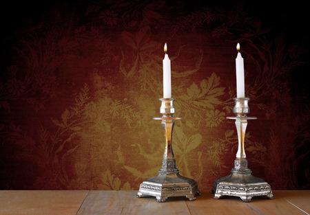 candela: due candelieri con candele accese sul tavolo di legno e sfondo d'epoca