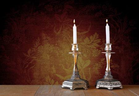 candles: two candlesticks with burning candles over wooden table and vintage background Stock Photo