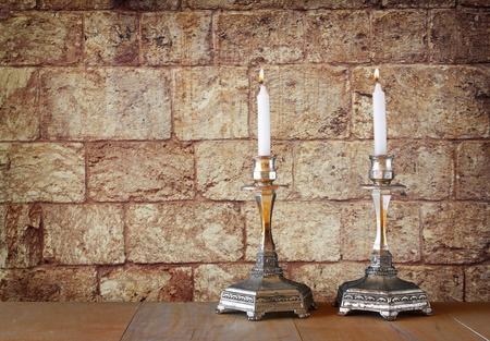 shabat: dos candelabros con velas encendidas sobre la mesa de madera y fondo antiguo muro de piedra de Jerusal�n