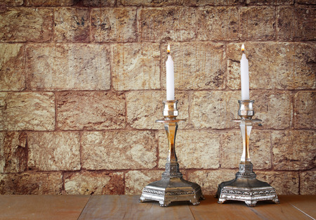 two candlesticks with burning candles over wooden table and old jerusalem stone wall background Stock Photo