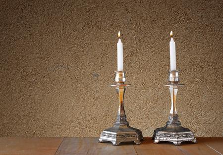 shabat: dos candelabros con velas encendidas sobre la mesa de madera y la pared de fondo con textura