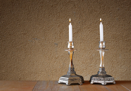 torah: two candlesticks with burning candles over wooden table and textured wall background