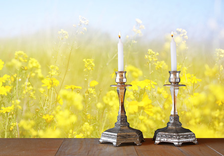 shabbat: two candlesticks with burning candles over wooden table and flower background