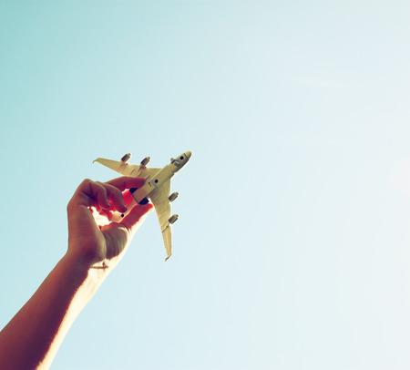 구름과 푸른 하늘을 배경으로 장난감 비행기를 들고 여자 손의 사진을 닫습니다