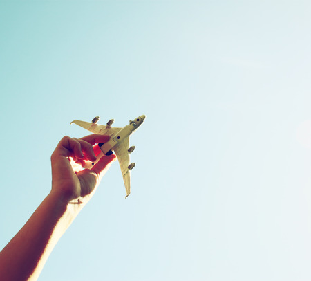close up photo of woman hand holding toy airplane against blue sky with clouds Standard-Bild