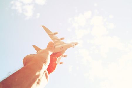 close up photo of man hand holding toy airplane against blue sky with clouds Stock Photo