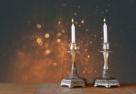 shabat: dos candelabros con velas encendidas sobre la mesa de madera y fondo del brillo de la vendimia