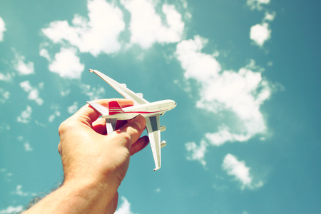 close up photo of man hand holding toy airplane against blue sky with clouds Stockfoto