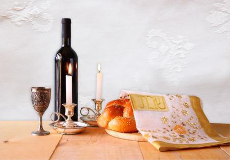 pan y vino: imagen shabbat. pan jalá, vino shabbat y candelas en mesa de madera.