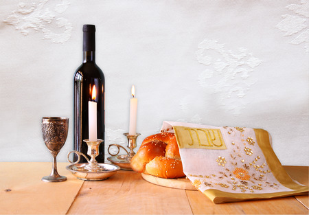shabbat image. challah bread, shabbat wine and candelas on wooden table.
